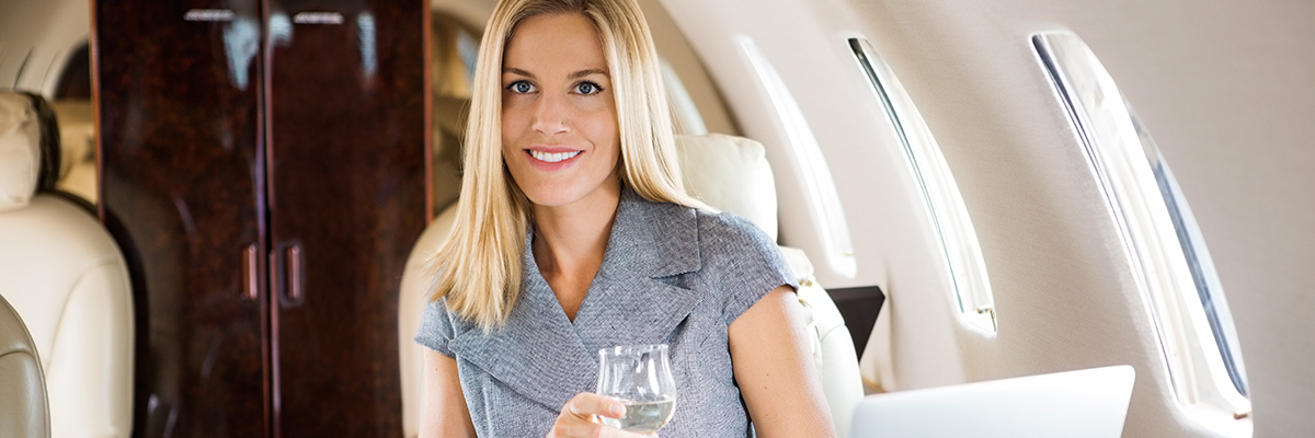 Businesswoman Having Wine In Corporate Jet
