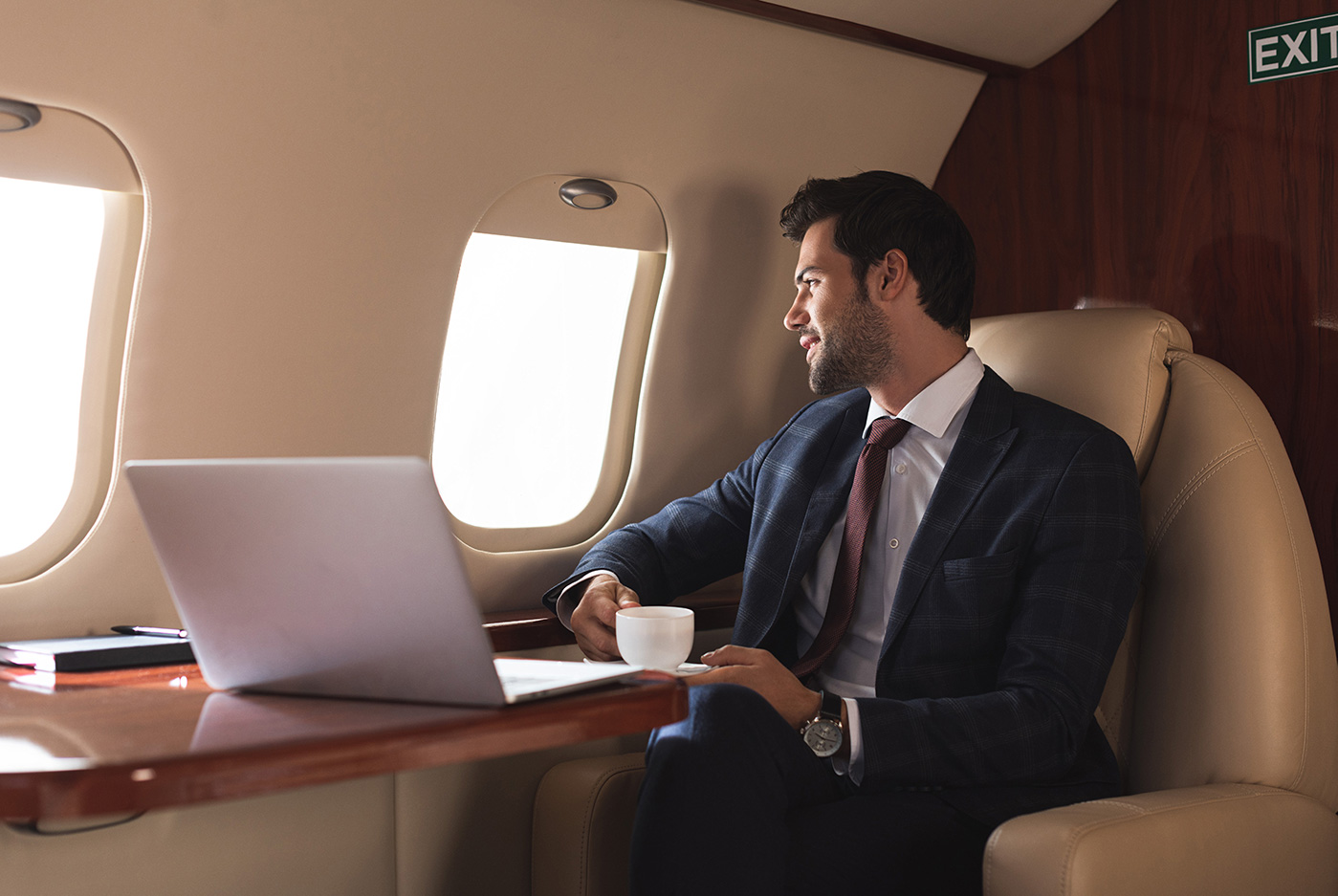 private jet benefits for the businessman looking out window on jet